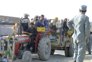 A tracktor and trailor with pashtun nomads, Kuchis, is waived through the check point near Gulridin by Afghan National Police